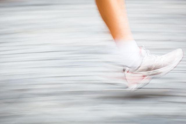 Motion blurred runner's feet in a city environment - running mar